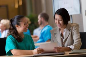 Hospital Administrator Interviewing Young Nurse For A Position.