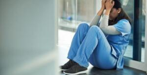 Shot Of A Young Doctor Sitting On The Floor And Looking Distraught