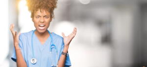 Young African American Doctor Woman Over Isolated Background Crazy And Mad Shouting And Yelling With Aggressive Expression And Arms Raised. Frustration Concept.